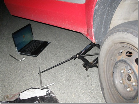 Changing a car tire by the light of a laptop screen